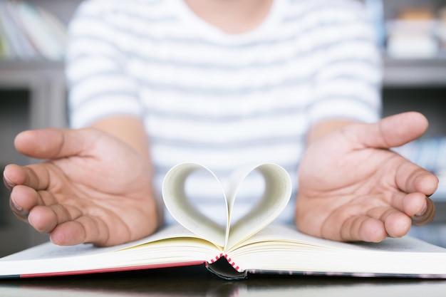 Homem abre o livro de show de mão com páginas abertas, dobre um pedaço de coração de papel na mesa de madeira na biblioteca.