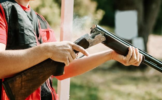 Homem abre o parafuso de espingarda depois de um tiro com fumaça