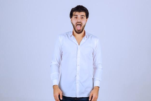 Homem abrindo a boca porque está com dor de garganta.