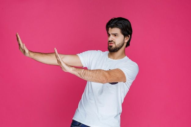 Homem abrindo as mãos e tentando parar algo.