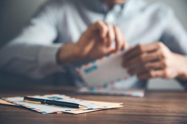 Homem abrindo e lendo cartas na mesa