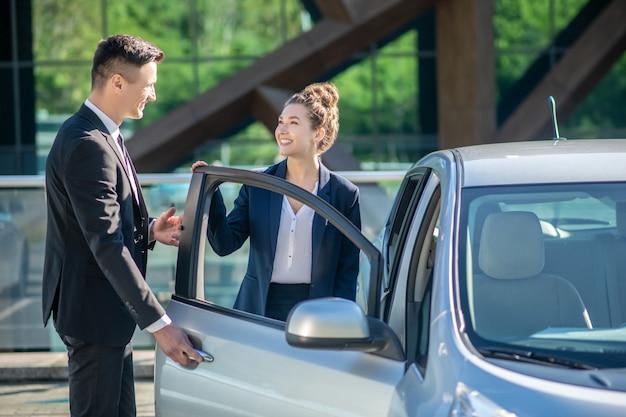 Homem abrindo uma porta de carro para uma mulher