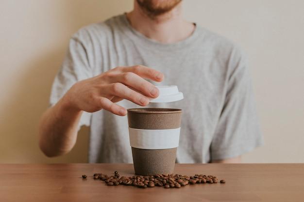 Homem abrindo uma xícara de café reutilizável