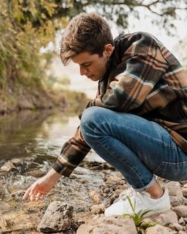 Homem acampando na floresta sentado à beira do rio