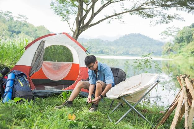 Homem acampar à beira do lago