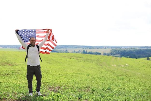 Homem acenando a bandeira americana em pé no campo agrícola de fazenda de grama, feriados, patriotismo, orgulho, liberdade, partidos políticos, imigrante