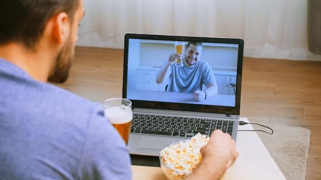 Homem acenando para o amigo durante uma chamada de vídeo em covid-19 e cerveja na mesa.