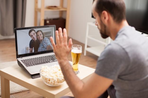 Homem acenando para seus amigos em uma videochamada durante a quarentena.