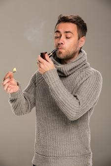 Homem acende um cachimbo com um fósforo no estúdio em um fundo cinza