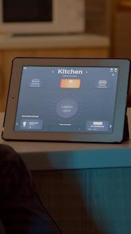 Homem acendendo as lâmpadas usando comando de voz no tablet