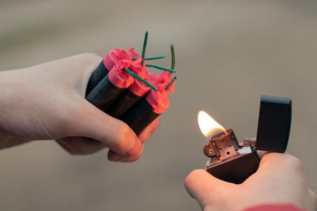 Homem acendendo vários fogos de artifício na mão usando o isqueiro a gasolina.