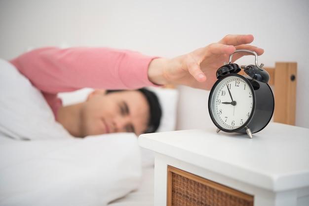 Homem acorda fazendo desligar o despertador de manhã