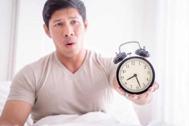 Homem acordou tarde e mostra despertador para a câmera