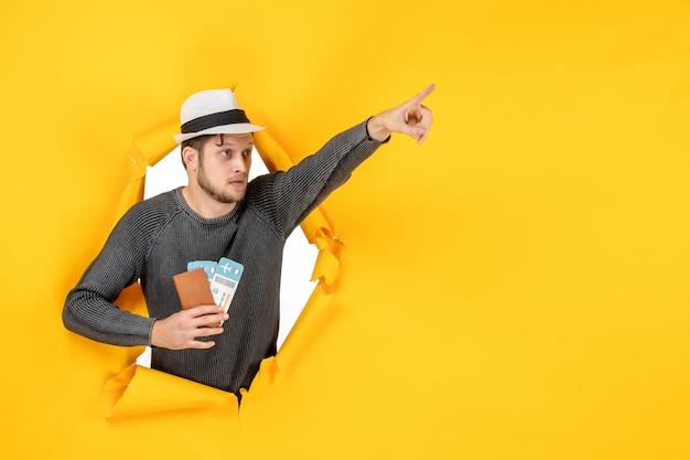 Homem admirado com um chapéu segurando um passaporte estrangeiro com passagem e apontando algo em uma parede amarela rasgada