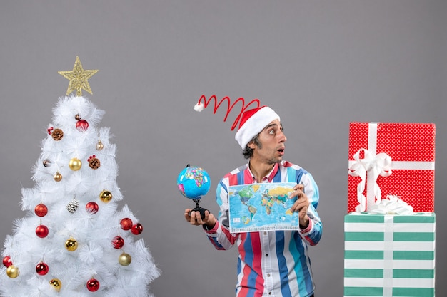 Homem admirado de vista frontal com chapéu de papai noel com mola espiral olhando para presentes segurando um mapa-múndi e um globo