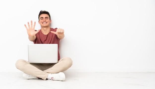 Homem adolescente sentado na flor com seu laptop contando seis com os dedos