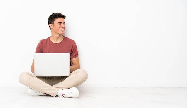 Homem adolescente sentado no chão com o laptop com os braços cruzados e feliz