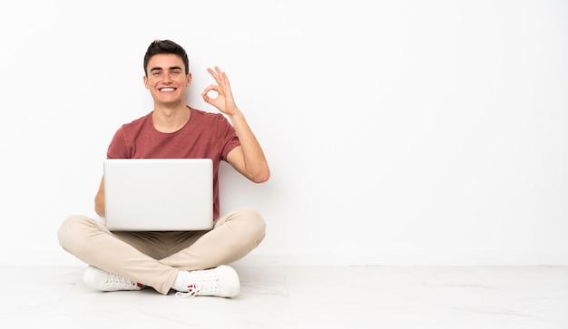 Homem adolescente sentado no chão com seu laptop mostrando sinal de ok com os dedos