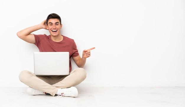Homem adolescente sentado no chão com seu laptop surpreso e apontando o dedo para o lado