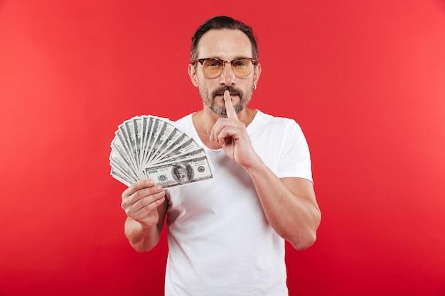 Homem adulto 30 anos de camiseta branca casual usando óculos, segurando o leque de dinheiro dólar em dinheiro e pedindo manter segredo ou silêncio com o dedo nos lábios, isolado sobre fundo vermelho