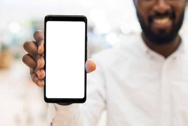 Homem adulto alegre preto mostrando o telefone móvel no fundo desfocado