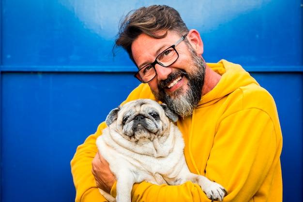 Homem adulto alegre sorri e abraça com amor seu próprio cachorro velho cão pug em um retrato com cor amarela e azul