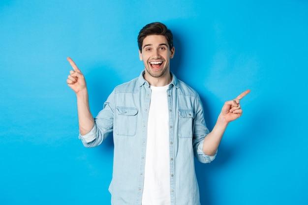 Homem adulto alegre sorrindo, apontando o dedo para o lado, mostrando banners promocionais à esquerda e à direita, em pé contra um fundo azul