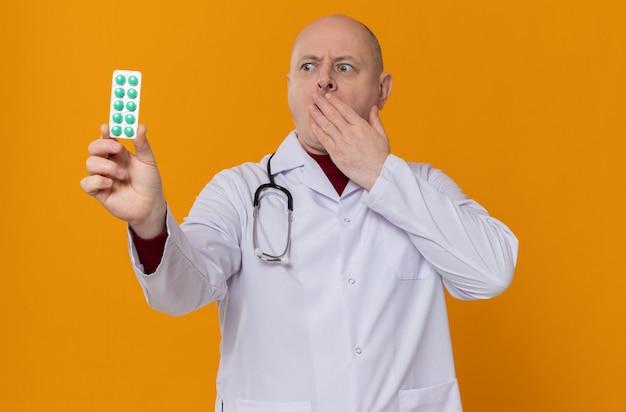 Homem adulto animado em uniforme de médico com estetoscópio segurando e olhando para a embalagem de remédio e colocando a mão na boca