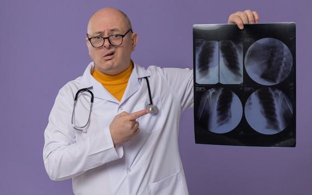 Homem adulto ansioso com óculos em uniforme de médico com estetoscópio segurando e apontando para o resultado do raio-x