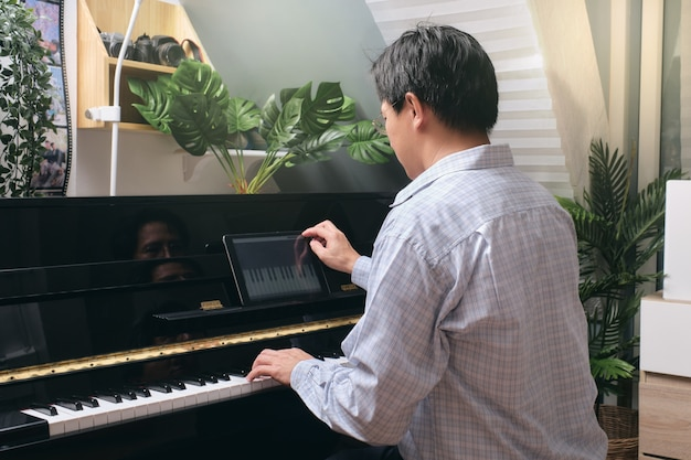 Homem adulto aprendendo a tocar piano usando tablet digital com aula on-line e curso na sala de estar em casa. feliz empresário asiático relaxando tocando piano