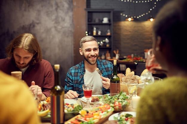 Homem adulto, aproveitando o jantar com os amigos
