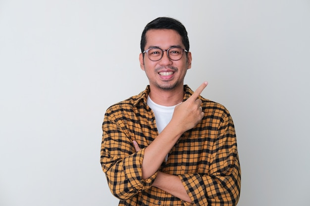 Homem adulto asiático apontando o dedo para a esquerda com uma cara sorridente