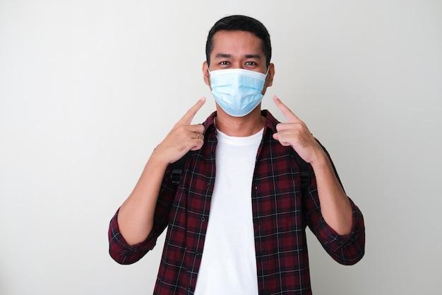Homem adulto asiático apontando sua máscara médica protetora