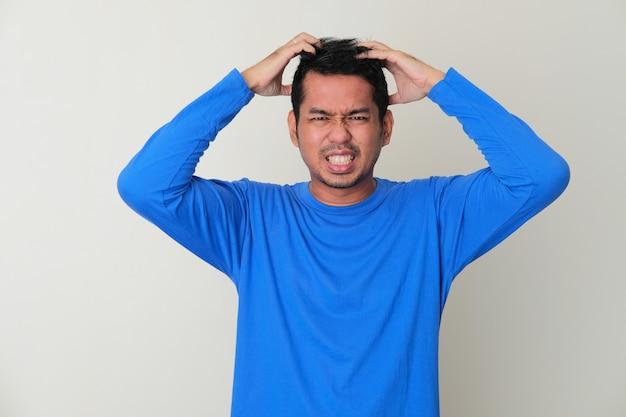 Homem adulto asiático com coceira no couro cabeludo