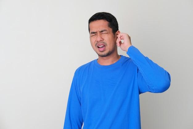 Homem adulto asiático com dor de ouvido dolorosa isolada no fundo branco