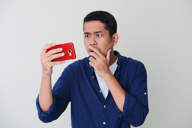 Homem adulto asiático com expressão de choque no rosto ao olhar para o celular