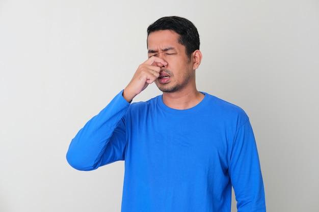 Homem adulto asiático com gesto de congestão nasal