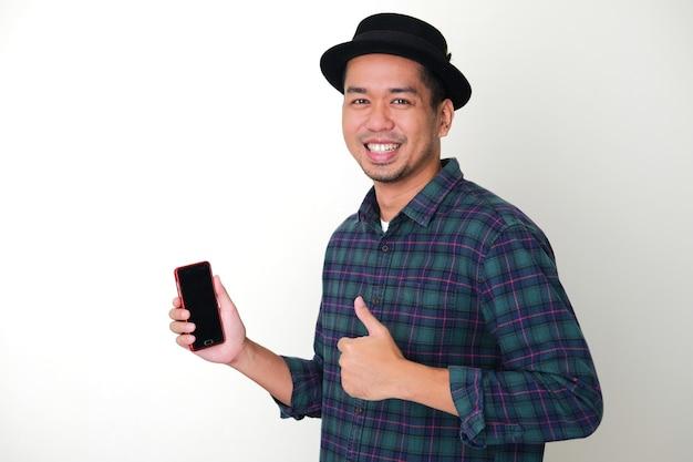 Homem adulto asiático desistindo do polegar ao segurar seu telefone celular com uma expressão feliz