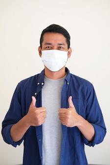 Homem adulto asiático fazendo dois polegares para cima enquanto usa máscara médica protetora