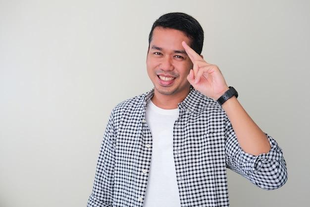 Homem adulto asiático fazendo um gesto de saudação enquanto sorri