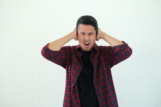 Homem adulto asiático fecha as orelhas com a mão e mostra uma expressão de raiva no rosto