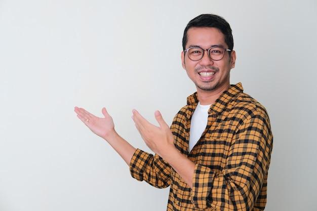 Homem adulto asiático mostrando algo por trás de um gesto com uma cara sorridente