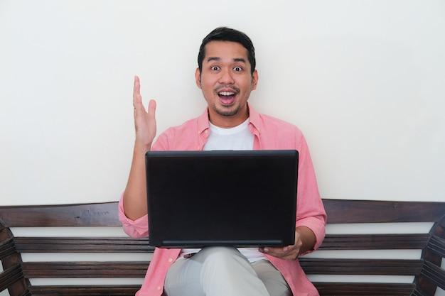 Homem adulto asiático mostrando expressão de entusiasmo no rosto ao trabalhar usando o laptop em sua casa