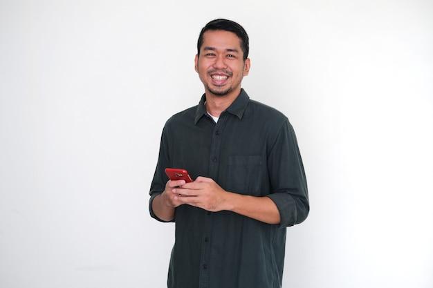 Homem adulto asiático mostrando expressão facial feliz ao segurar seu telefone celular