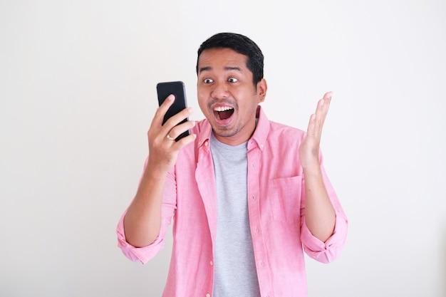 Homem adulto asiático mostrando expressão facial feliz enquanto olha para a tela do celular