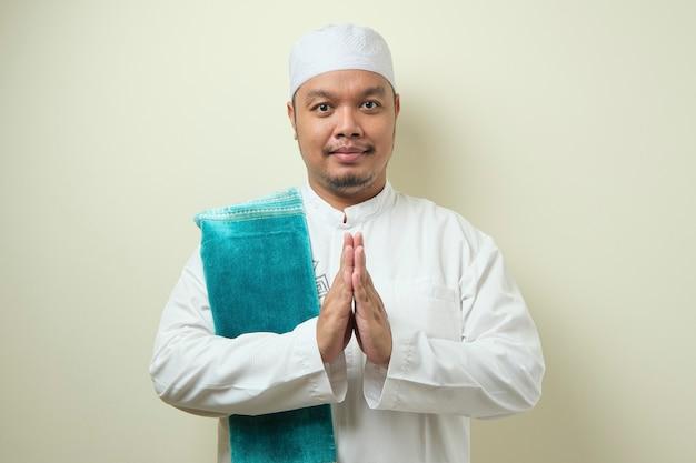 Homem adulto asiático muçulmano gesticulando para saudar e dar as boas-vindas ao eid mubarak