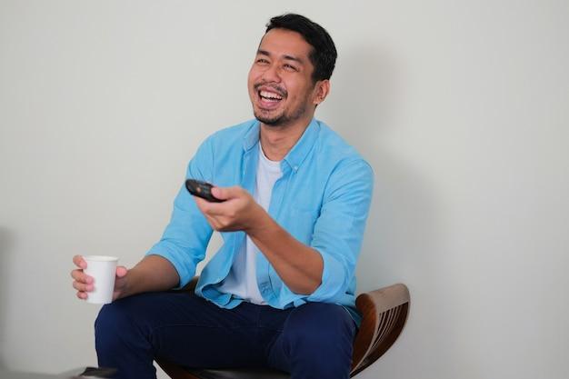 Homem adulto asiático rindo muito ao assistir televisão