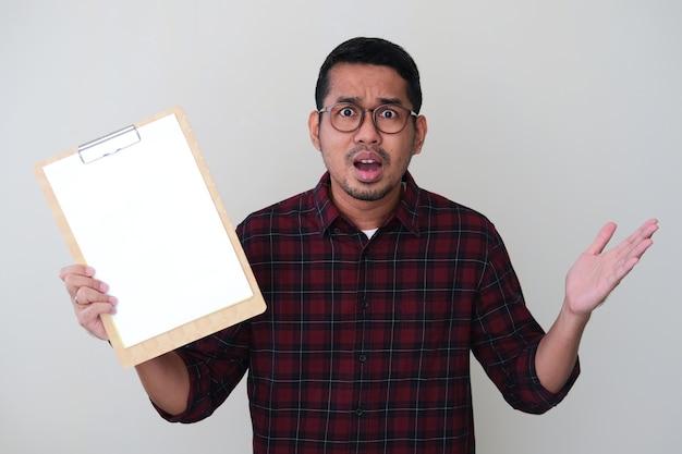 Homem adulto asiático segurando um papel branco em branco e mostrando uma expressão facial confusa