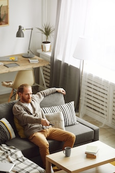 Homem adulto assistindo tv em casa
