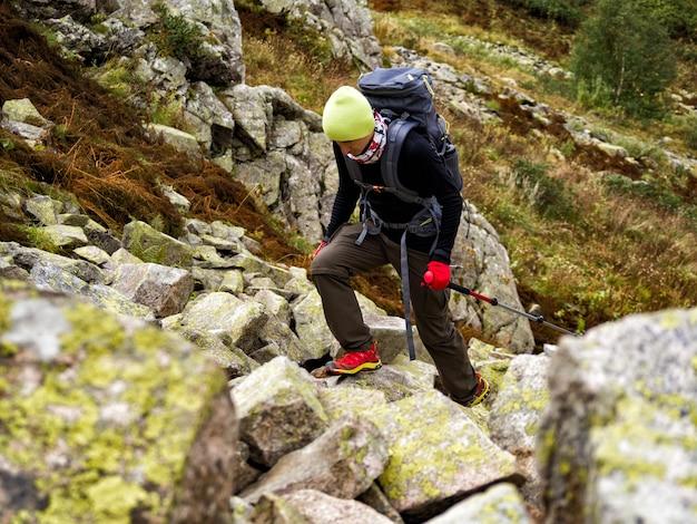 Homem adulto ativo com mochila e bastões de trekking, caminhando no rio de pedras rochosas